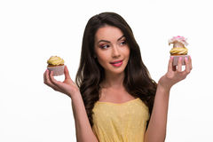 Girl doubts between two yummy cupcakes Stock Images