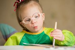Girl with Down syndrome covered in paint when drawing stock photos