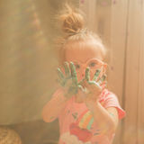 Girl with Down syndrome covered in paint when drawing stock image