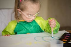 Girl with Down syndrome covered in paint when drawing stock photography