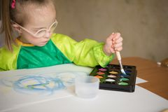 Girl with Down syndrome covered in paint when drawing stock images