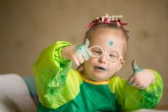 Girl with Down syndrome covered in paint when drawing royalty free stock photos