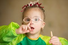 Girl with Down syndrome  covered in paint when drawing. Girl with Down syndrome covered in paint when drawing Royalty Free Stock Images