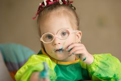 Girl with Down syndrome covered in paint when drawing royalty free stock images