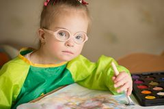 Girl with Down syndrome draws paints royalty free stock image
