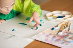 Girl with Down syndrome draws paints royalty free stock photo