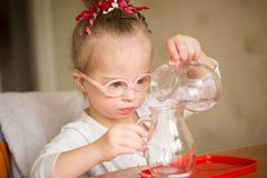 Girl with Down syndrome  gently pours water from a jug into a jug Royalty Free Stock Photos