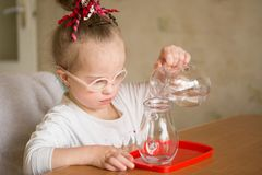 Girl with Down syndrome  gently pours water from a jug into a jug. Girl with Down syndrome gently pours water from a jug into a jug Stock Image