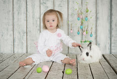 Girl with Down Syndrome holding the ear easter bunny. Little girl with Down Syndrome holding the ear easter bunny Royalty Free Stock Images