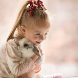 Girl with Down syndrome  hugs rabbit. Girl with Down syndrome hugs rabbit Stock Photography