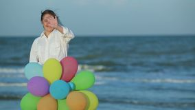 Girl with Down syndrome. Girl with intellectual impairment, Down syndrome, holding baloons and waving hands stock footage