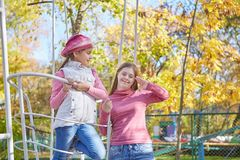 Girl with Down syndrome and little girl in autumn park. royalty free stock photography