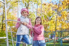 Girl with Down syndrome and little girl in autumn park. royalty free stock images
