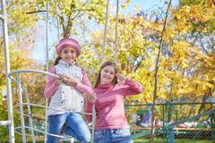 Girl with Down syndrome and little girl in autumn park. stock photography