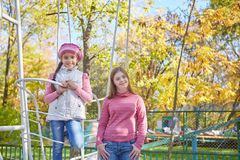 Girl with Down syndrome and little girl in autumn park. stock photos