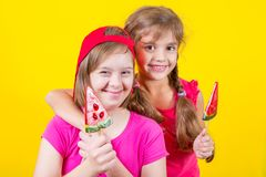 Girl Down syndrome and little girl with large Lollipop. Studio portrait on yellow background royalty free stock image