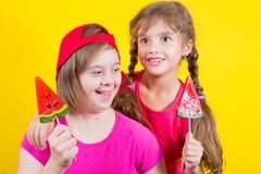 Girl Down syndrome and little girl with large Lollipop royalty free stock images