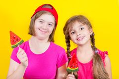 Girl Down syndrome and little girl with large Lollipop. Studio portrait on yellow background royalty free stock images