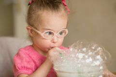 Girl with Down syndrome makes breathing speech therapy exercise royalty free stock images