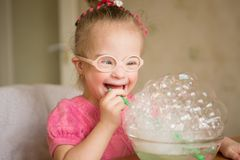 Girl with Down syndrome  makes breathing speech therapy exercise. Girl with Down syndrome makes breathing speech therapy exercise Stock Image