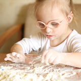 Girl with Down syndrome playing flour Royalty Free Stock Images