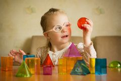 Girl with Down syndrome playing with geometrical shapes royalty free stock photography