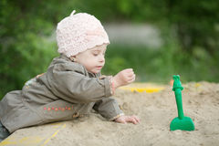 Girl with Down syndrome playing in the sandbox Stock Photography