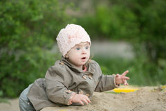 Girl with Down syndrome  playing in the sandbox. Girl with Down syndrome playing in the sandbox Stock Photos