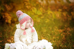 Girl with Down syndrome is resting in autumn park Royalty Free Stock Photos