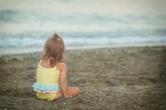 Girl with Down syndrome sitting on the beach Stock Image