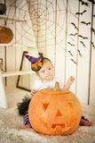 Girl with Down syndrome sitting near a big orange pumpkin Stock Photos