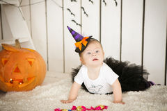 Girl with Down syndrome sitting near a big orange pumpkin Stock Photography