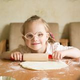 Girl with down syndrome unrolls dough royalty free stock photography