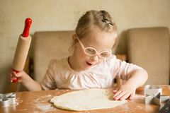 Girl with down syndrome unrolls dough royalty free stock photo