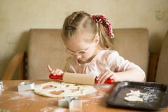 Girl with down syndrome unrolls dough stock photography