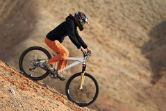 Girl downhill on mountain bike. In red canyon Royalty Free Stock Photography