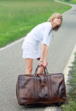 Girl dragging a leather suitcase Royalty Free Stock Photos