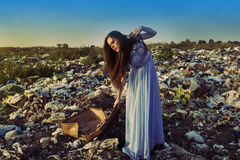 A girl drags a heavy suitcase on a garbage dump Royalty Free Stock Photography