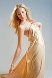 Girl in the drapery. Beautiful seductive girl in golden drapery Royalty Free Stock Photo