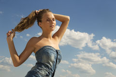 Girl draw back her hair into a ponytail over blue sky Stock Photos