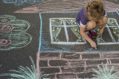 Girl draw house with chalk on asphalt Royalty Free Stock Photos