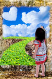 Girl draw nature with paintbrush on grunge wall background. Little asian girl drawing beautiful nature with paintbrush, heart-shaped clouds, blue sky, green Royalty Free Stock Image
