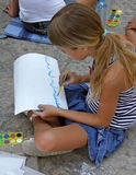 Girl draw a sea on asphalt. Alone young blond girl, - female sitting on floor - drawing on asphalt with water color. Vertical color photo Stock Photos