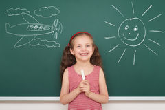 Girl draw sun and plane on board Stock Images