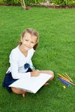 Girl drawing. Little cute girl drawing with crayons sitting on a green lawn Royalty Free Stock Photos