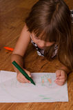 Girl drawing. Girl laying on floor drawing Royalty Free Stock Photo