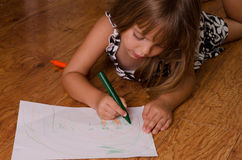 Girl drawing. Girl coloring laying on the kitchen floor Stock Images
