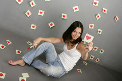 Girl drawing around the heart shape. Girl with painted hearts on the wall stickers. White T-shirt and  jeans on a beautiful girl in love Stock Images