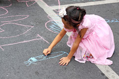 Girl drawing on asphalt Stock Image