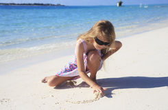 Girl drawing in beach sand. A view of a young girl drawing pictures and writing in the wet sand of a seaside beach stock image